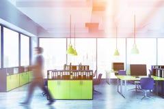 Homme dans le bureau bleu et jaune avec des bibliothèques image stock
