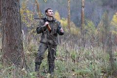 Homme dans le camouflage et avec des armes à feu dans une ceinture de forêt sur un hun de ressort Photographie stock libre de droits