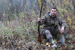 Homme dans le camouflage et avec des armes à feu dans une ceinture de forêt sur un hun de ressort Image libre de droits