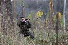 Homme dans le camouflage et avec des armes à feu dans une ceinture de forêt sur un hun de ressort Photos libres de droits