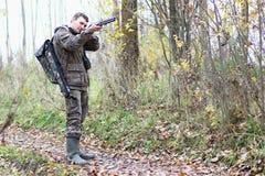 Homme dans le camouflage et avec des armes à feu dans une ceinture de forêt sur un hun de ressort Photos stock