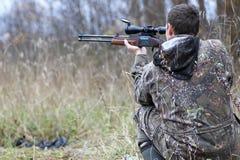 Homme dans le camouflage et avec des armes à feu dans une ceinture de forêt sur un hun de ressort Photo stock