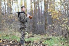 Homme dans le camouflage et avec des armes à feu dans une ceinture de forêt sur un hun de ressort Image stock