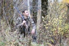 Homme dans le camouflage et avec des armes à feu dans une ceinture de forêt sur un hun de ressort Images libres de droits