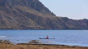 Homme dans le canoë se déplaçant lentement près de la montagne banque de vidéos