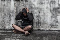 Homme dans le capot avec des mains sur sa tête Image libre de droits