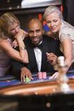 Homme dans le casino avec les femmes fascinants Photographie stock libre de droits