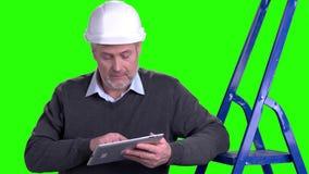 Homme dans le casque antichoc utilisant le comprimé numérique clips vidéos