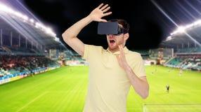 Homme dans le casque de réalité virtuelle au-dessus du terrain de football Photo stock