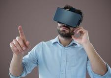 Homme dans le casque de réalité virtuelle sur le fond brun Photos libres de droits