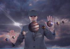 Homme dans le casque de VR touchant les planètes 3D contre le ciel pourpre avec des nuages et des fusées Image stock