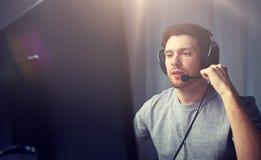 Homme dans le casque jouant le jeu vidéo d'ordinateur à la maison Images stock