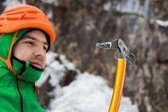 Homme dans le casque orange regardant la hache de glace sur le backgrou de roche et de glace Photos stock