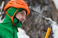 Homme dans le casque orange regardant la hache de glace sur le fond de roche et de glace Images libres de droits