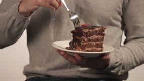 Homme dans le chandail mangeant un grand morceau de gâteau de chocolat banque de vidéos