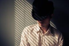 Homme dans le chapeau à côté de la fenêtre Image stock