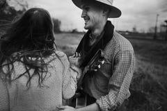 Homme dans le chapeau avec la guitare regardant et souriant à sa femme de boho dedans Photos stock