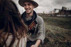 Homme dans le chapeau avec la guitare regardant et souriant à sa femme de boho dedans Photo libre de droits