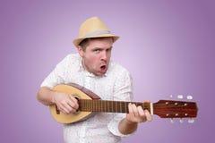 Homme dans le chapeau d'été jouant la guitare et chantant des chansons photographie stock libre de droits