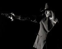 Homme dans le chapeau de cowboy orientant le pistolet. Photo stock