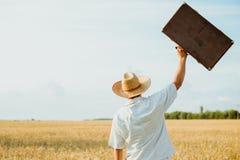 Homme dans le chapeau de paille jetant en l'air vers le haut d'une rétro valise Photos stock