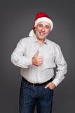 Homme dans le chapeau de Santa affichant des pouces vers le haut Image stock