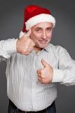 Homme dans le chapeau de Santa affichant des pouces vers le haut Photographie stock