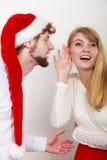 Homme dans le chapeau de Santa chuchotant à l'oreille de femme Photo libre de droits