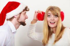 Homme dans le chapeau de Santa chuchotant à l'oreille de femme Photo stock