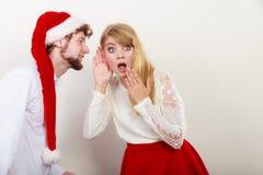 Homme dans le chapeau de Santa chuchotant à l'oreille de femme Photographie stock