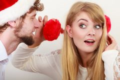 Homme dans le chapeau de Santa chuchotant à l'oreille de femme Photographie stock libre de droits