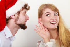 Homme dans le chapeau de Santa chuchotant à l'oreille de femme images stock