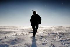 Homme dans le chapeau de Santa marchant sur la zone de neige Photographie stock libre de droits