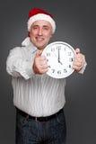 Homme dans le chapeau de Santa retenant l'horloge Photographie stock