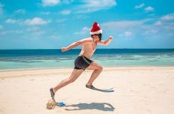 Homme dans le chapeau de Santa sur la plage tropicale Image libre de droits