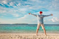 Homme dans le chapeau de Santa sur la plage tropicale Photographie stock libre de droits