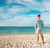 Homme dans le chapeau de Santa sur la plage tropicale Photo libre de droits