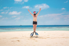 Homme dans le chapeau de Santa sur la plage tropicale Photos libres de droits