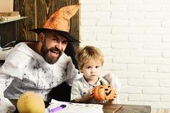 Homme dans le chapeau et l'enfant oranges avec les visages heureux et intéressés images libres de droits