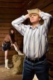Homme dans le chapeau et la femme de cowboy restant le mur proche Photographie stock libre de droits