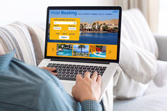 Homme dans le clavier de dactylographie d'ordinateur portable de pièce avec l'écran de réservation d'hôtel