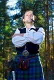 Homme dans le costume écossais avec l'épée et la pipe image stock