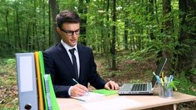 Homme dans le costume écrivant des idées d'affaires, se reposant au bureau dans le parc ensoleillé, inspiration image libre de droits