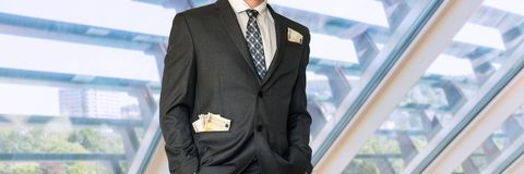 Homme dans le costume avec l'argent dans des poches Images stock