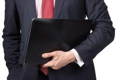 Homme dans le costume avec l'ordinateur portable Images stock