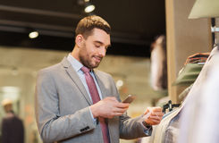 Homme dans le costume avec le smartphone au magasin d'habillement Photographie stock