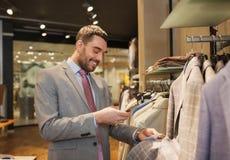 Homme dans le costume avec le smartphone au magasin d'habillement Images libres de droits