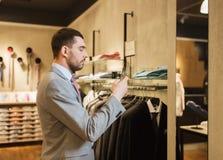 Homme dans le costume avec le smartphone au magasin d'habillement Image libre de droits