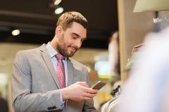 Homme dans le costume avec le smartphone au magasin d'habillement Photographie stock libre de droits