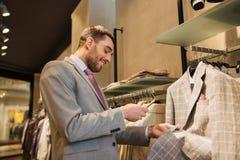 Homme dans le costume avec le smartphone au magasin d'habillement Image stock